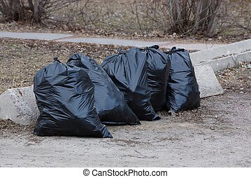 black plastic bags of garbage are standing on the gray asphalt on the sidewalk