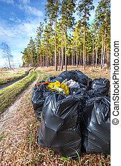 Black plastic bags of garbage in the woods. Siberia, Russia
