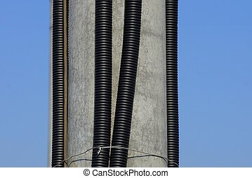 black plastic hoses with electrical cables on a gray concrete pillar