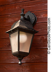 black plastic lantern with a white light bulb on a wooden wall