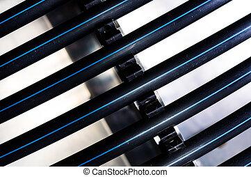 Black plastic pipes against white background