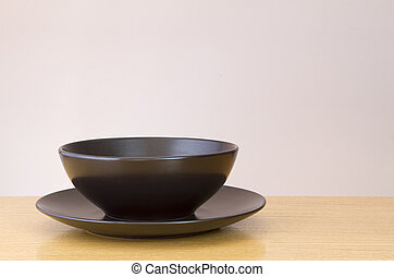 Black plate and bowl on  wooden table