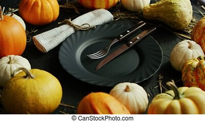 Black plate and cutlery surrounded by pumpkins - From above...