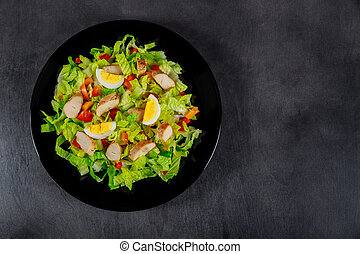 Black plate of chicken salad on a wooden table