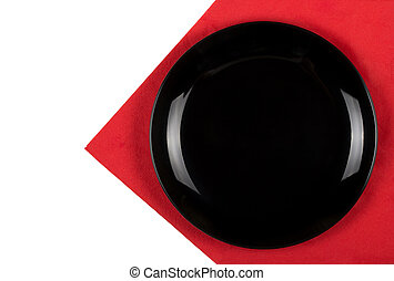 Black plate on a red napkin