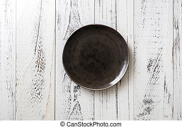 Black Plate on white wooden background