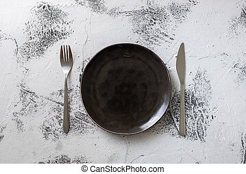 Black Plate on white wooden background with utensils