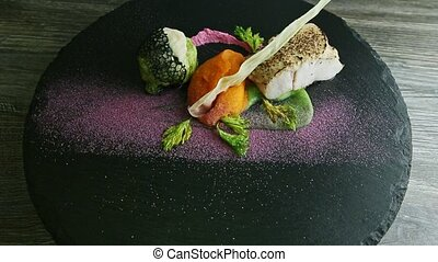 black plate with exquisite decorated white sea fish, carrot puree, baked vegetables, and sauces spinning around on wooden table