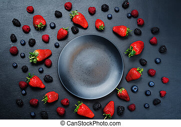 Black plate with fruits and berries
