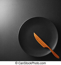 Black plate with knife on a background.