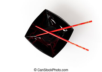 Black plate with red chopsticks isolated