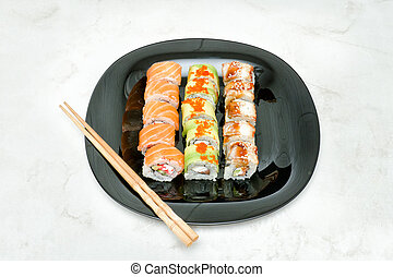 Black plate with various rolls and chopsticks. Top view