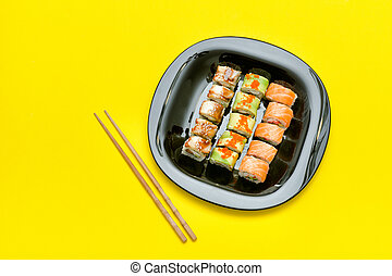 Black plate with various rolls on a yellow background. Top view