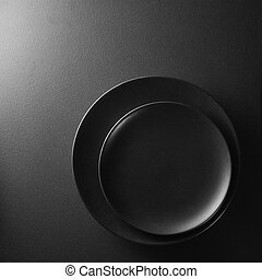 Black plates on a background. - Black plates on a textured...