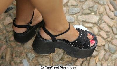 Black platform shoes on womans foots