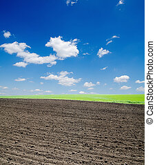 black ploughed field and cloudy sky