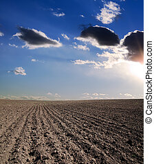 black ploughed field under blue cloudy sky