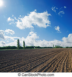 black ploughed field under blue sky with sun