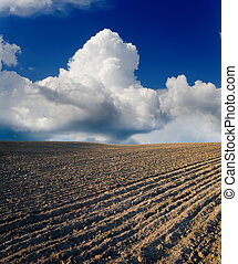 black ploughed field under cloudy sky