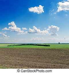 black ploughed field under deep blue sky