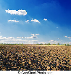 black ploughed field under deep blue sky with clouds