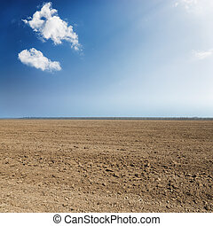 black plowed agriculture field and blue sky with clouds