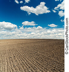 black plowed field after harvesting and blue cloudy sky