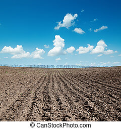 black plowed field after harvesting under blue sky