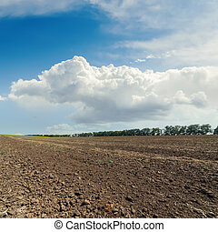 black plowed field and cloudy sky