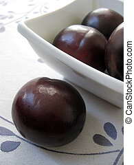 Black Plum - Freshly picked black plum with a small bowl of...