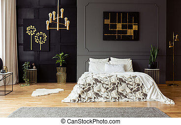 Black poster on grey wall above bed with white pillows in dark bedroom interior with plants. Real photo