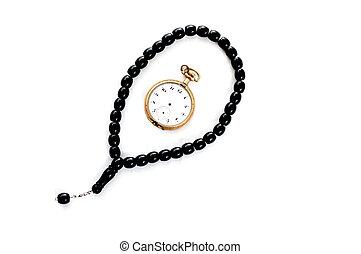 prayer beads and vintage pocket clock, time for praying