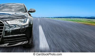 Black prestigious car on the road.