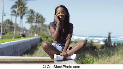 Black pretty woman talking on phone at fence - Attractive...