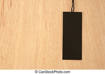 Black price label tag on wooden background