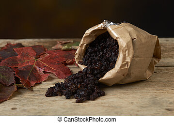 Black raisins in paper bags on a wooden table