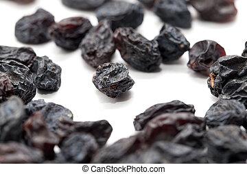 Black raisins on a white background. macro