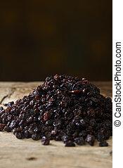 Black raisins over wooden table