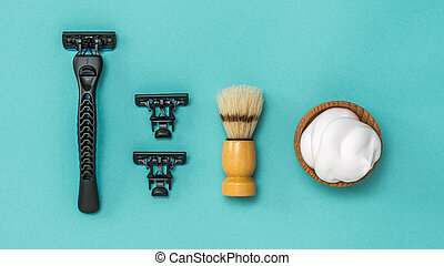 Black razor with two replacement blades and a shaving brush for shaving on a blue background. Flat lay.