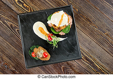 Black rectangle plate with food, top view.