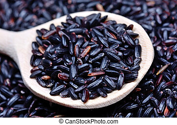 Black rice in a wooden spoon