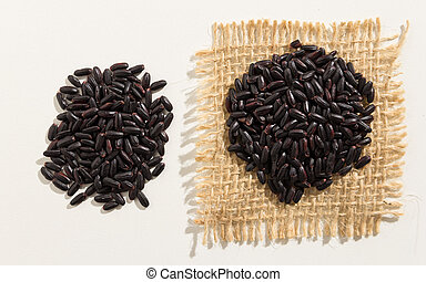 Black Rice seed. Close up of grains spreaded over white table.