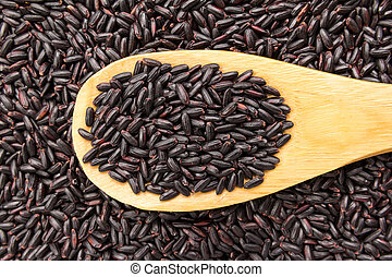 Black Rice seed. Grains in wooden spoon. Close up.