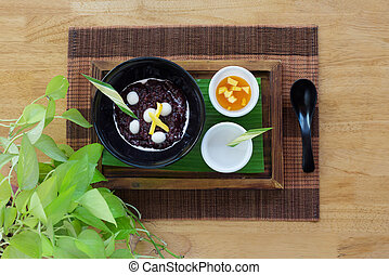 Black rice sweet pudding on wooden background.