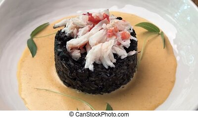 black rice with crab meat on a white plate