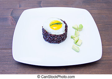 Black rice with quail egg on a wooden table