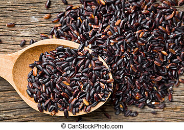 black rice with wooden spoon on wooden table