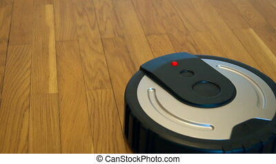 Black robotic vacuum cleaner on the floor.