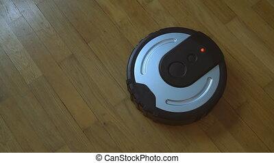 Black robotic vacuum cleaner on the floor.