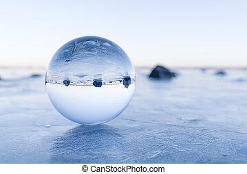 Black rocks in a glass orb on a frozen lake